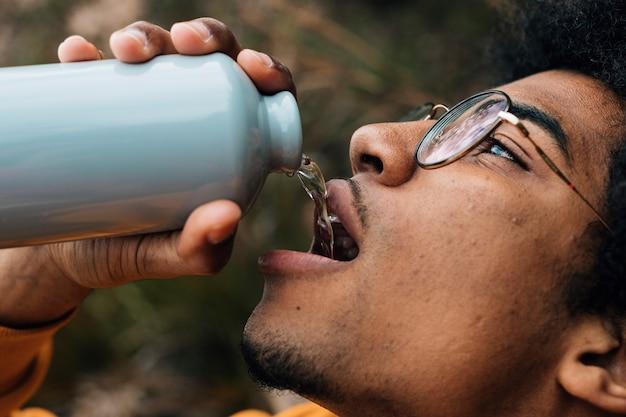 Tragende brillen des männlichen wanderergesichtes, die das wasser von der flasche trinken