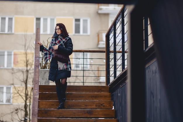 Tragende brillen eines mädchens im winter trägt hölzerne treppe