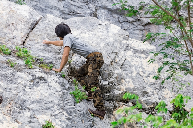 Tragende cargo-hosen des mannes und klettern auf dem felsen