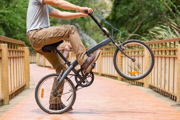 Tragende cargo-hosen des mannes und sein fahrrad