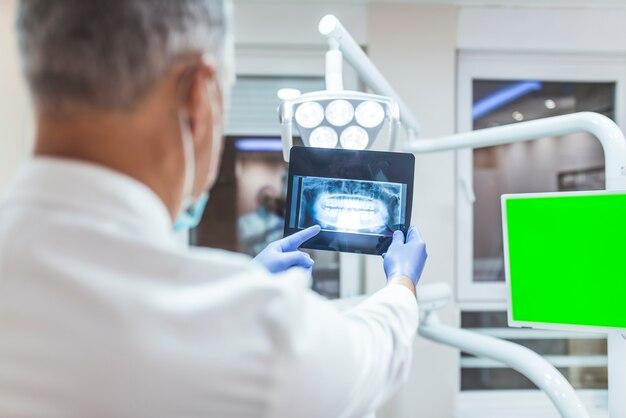 Tragende chirurgische maske des zahnarztes den röntgenstrahl studierend.