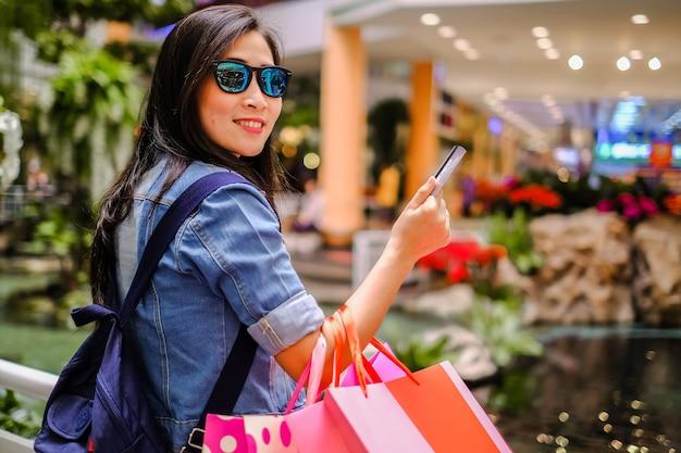 Tragende einkaufstasche asien-schönheit, die kreditkarte hält