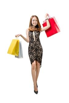 Tragende einkaufstascheaufstellung der glücklichen asiatischen frau