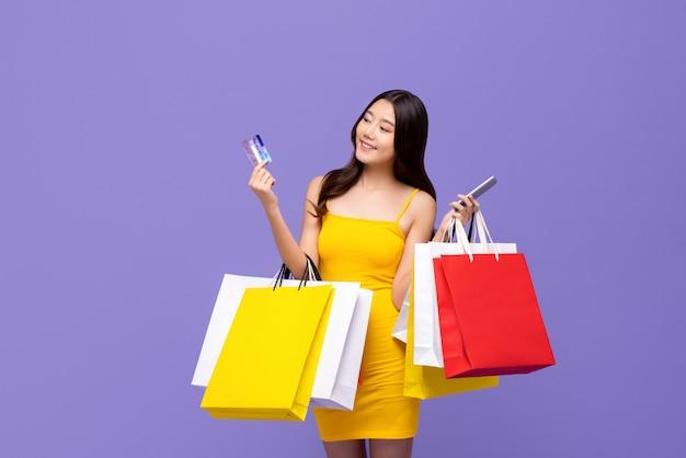 Tragende einkaufstaschen der asiatin mit kreditkarte und smartphone in den händen
