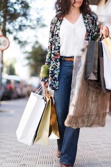 Tragende einkaufstaschen der frau auf straße