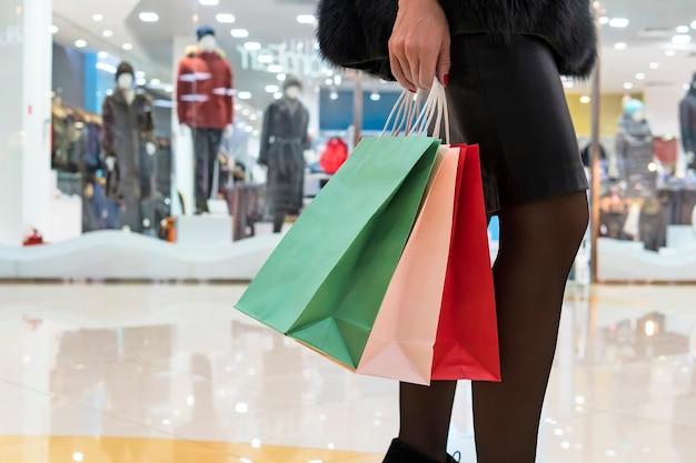 Tragende einkaufstaschen der jungen frau beim gehen im einkaufszentrum. nahaufnahme der hand der dame, die einige pakete mit neukäufen hält. mädchen, nachdem geld in der boutique ausgegeben wurde. konzept des weiblichen einkaufens.