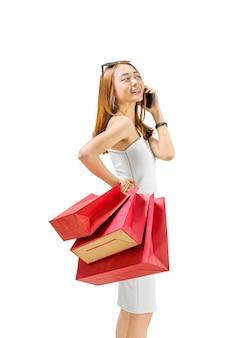 Tragende einkaufstaschen der recht asiatischen frau bei der unterhaltung auf smartphone