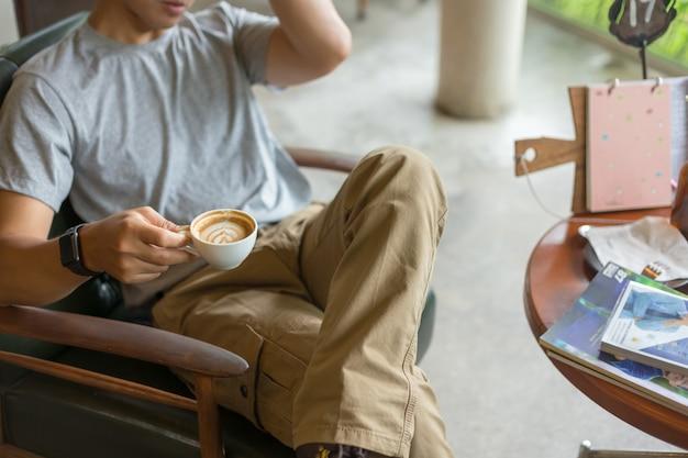 Tragende frachthosen des kerls und trinken eines kaffees in der kaffeestube