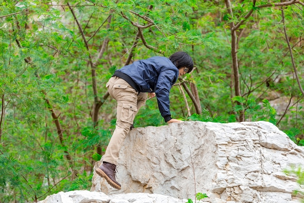 Tragende frachthosen des mannes und klettern auf dem felsen