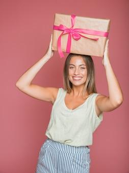 Tragende geschenkbox der glücklichen frau über ihrem kopf gegen farbigen hintergrund