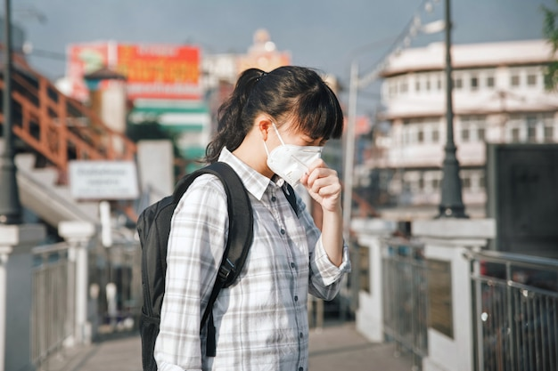 Tragende gesichtsmaske der asiatin, die wegen der luftverschmutzung in der stadt husten