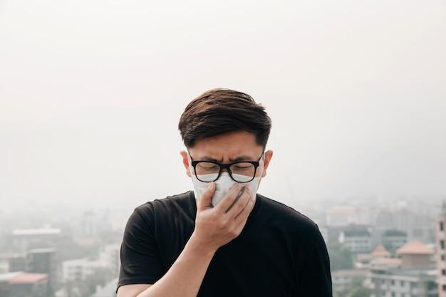Tragende gesichtsmaske des asiatischen mannes wegen der luftverschmutzung in der stadt.