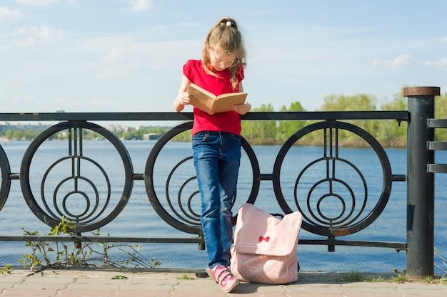Tragende gläser der kinderstudentin mit rucksack liest buch