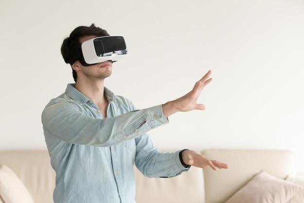 Tragende gläser der virtuellen realität des jungen mannes, vr-kopfhörer für smartp