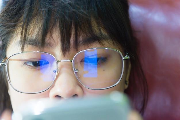 Tragende gläser des asiatischen mädchens liegen auf sofa unter verwendung eines smartphone.