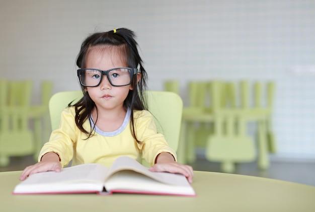 Tragende gläser des klugen kleinen kindermädchens, die ein buch im kinderraum lesen.
