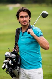 Tragende golfclubs des erwachsenen mannes draußen