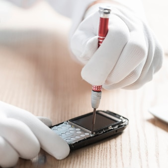 Tragende handschuhe des männlichen technikers, die mobiltelefon reparieren