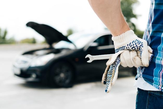 Tragende handschuhe des mannes, die schlüssel halten