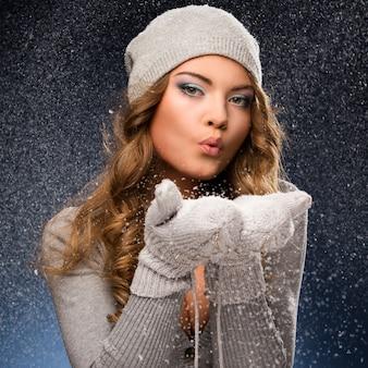 Tragende handschuhe des netten gelockten mädchens während der schneefälle