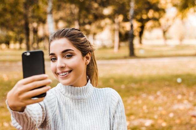 Tragende herbstausstattung der schönen blonden jugendlichen im park, der selfie nimmt.