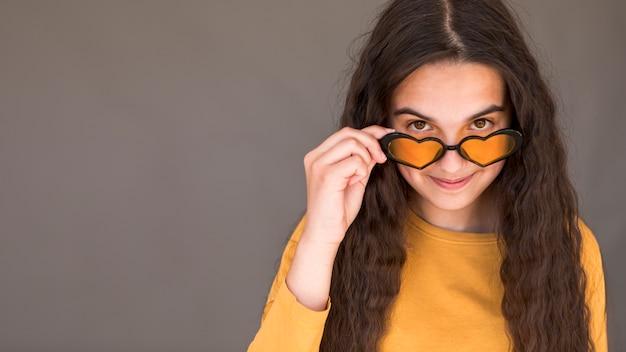 Tragende herzsonnenbrille des mädchens mit kopienraum