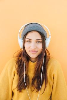 Tragende hörende musik des sweatshirts der frau auf kopfhörern