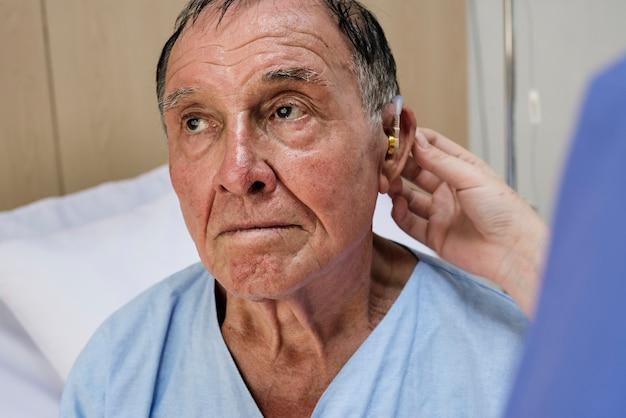 Tragende hörgeräte des alten mannes
