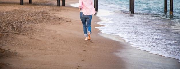 Tragende jeans der frau, die am sunet auf dem strandsand laufen