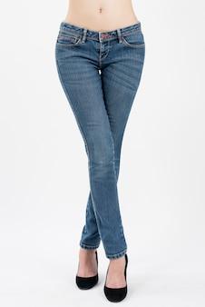 Tragende jeans der frau mit den beinen kreuzten in der vorderansichthalblänge, die auf weißem hintergrund lokalisiert wurde