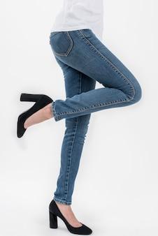Tragende jeans der frau und die aufstellung des weißen t-shirts heben ihr bein in der vorderansichthalblänge an, die auf weißem hintergrund lokalisiert wird