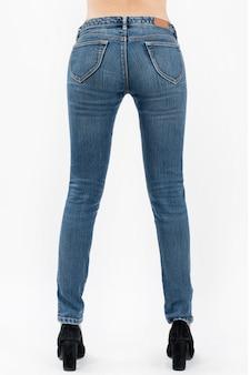 Tragende jeans der frau, welche die seitenansicht halbwegs lokalisiert auf weißem hintergrund aufwerfen
