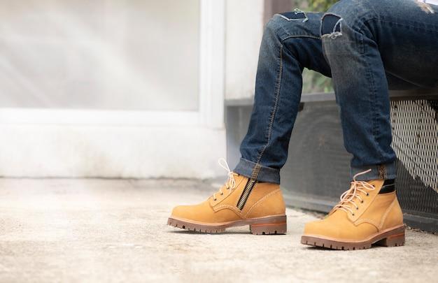 Tragende jeans des mannmodells und braune lederstiefel