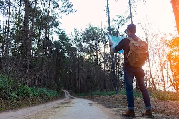 Tragende jeans und lederstiefel des einsamen mannes, die entlang den weg gestreut mit felsen gehen.