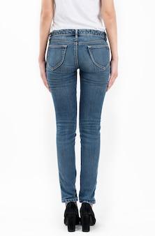 Tragende jeans und weißes t-shirt der frau, welche die seitenansichthälfte lokalisiert auf weißem hintergrund steht