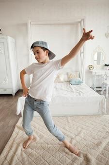 Tragende kappe des kleinen jungen und tanzen in schlafzimmer