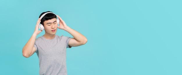 Tragende kopfhörer des asiatischen mannes, die emotionale musik hören