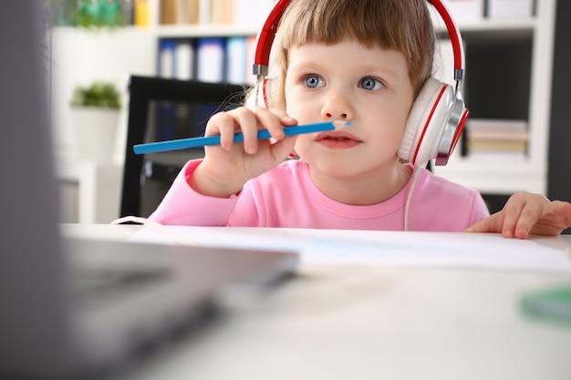 Tragende kopfhörer des kleinen mädchens benutzen mobilen computer