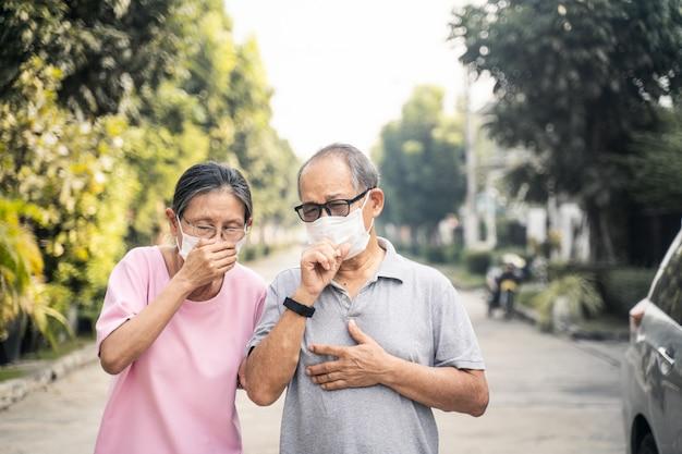 Tragende maske der asiatischen älteren älteren paare für verhindern dämmerung pm 2,5 schlechte luftverschmutzung, die husten wegen der schlechten luftverschmutzung hat.