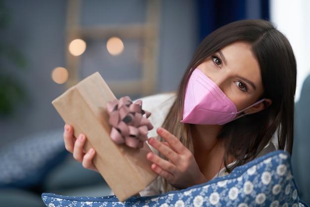 Tragende maske der erwachsenen frau, die zu hause herz hält, valentinsgrußkonzept