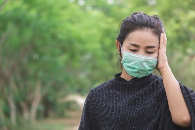 Tragende maske der kranken asiatin, die kopfschmerzen hat
