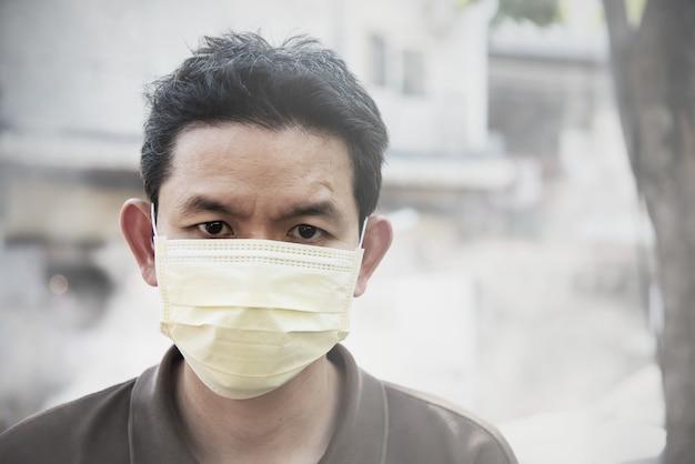 Tragende maske des mannes schützen feinstaub in der luftverschmutzungsumwelt