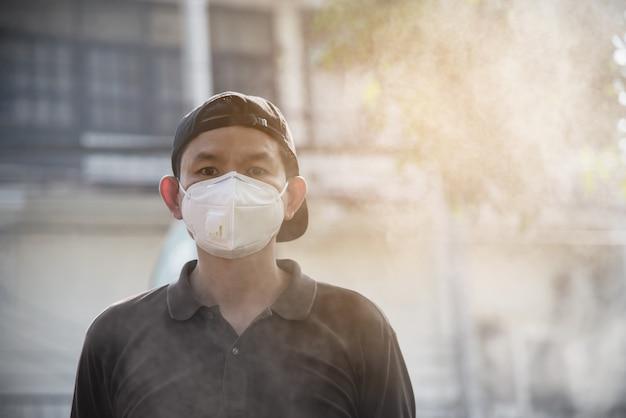 Tragende maske des mannes schützen sich in der luftverschmutzungsumwelt