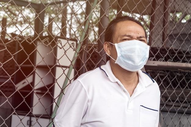 Tragende mundmaske des asiatischen mannes gegen luftverschmutzung.