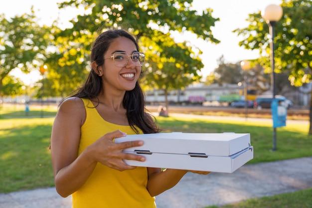 Tragende pizza des glücklichen lateinischen weiblichen kuriers im park