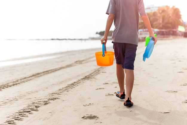 Tragende plastikspielwaren des jungen, die entlang den strand gehen.
