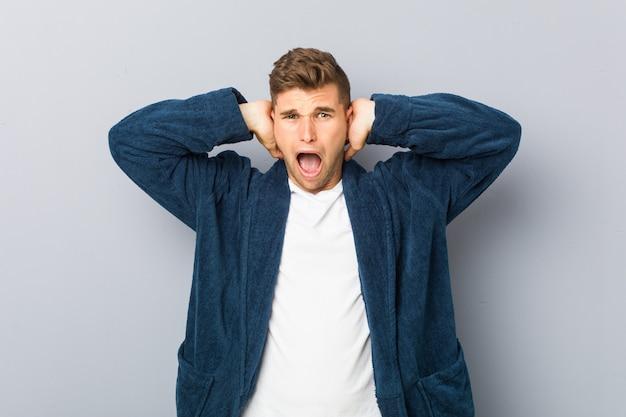 Tragende pyjama-bedeckungsohren des jungen kaukasischen mannes mit den händen, die versuchen, nicht zu lauten ton zu hören.