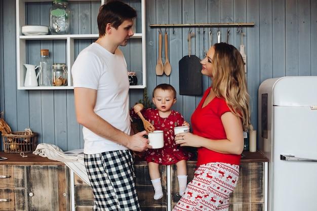 Tragende pyjamas der glücklichen familie weihnachts, die zusammen mit kleiner tochter kochen.