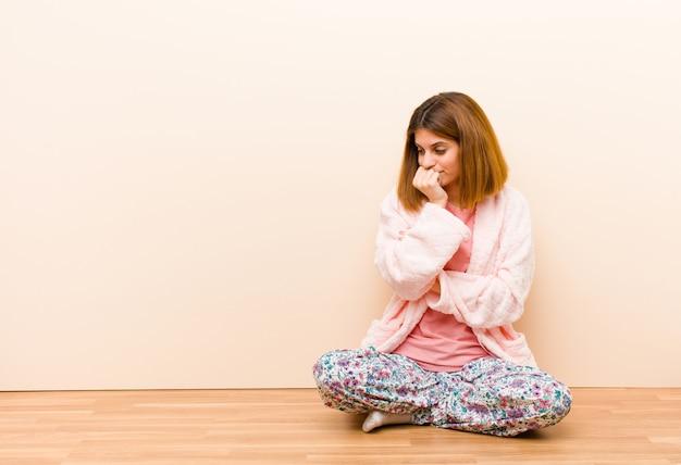 Tragende pyjamas der jungen frau, die zu hause das gefühl ernst, durchdacht und betroffen sitzen und seitlich mit der hand anstarren, die gegen kinn gedrückt wird