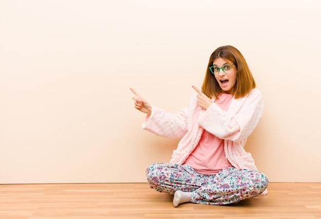 Tragende pyjamas der jungen frau, die zu hause fühlen froh und überrascht sitzen, mit einem entsetzten ausdruck lächeln und auf die seite zeigen